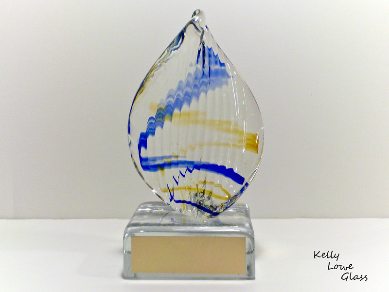 "<p></p> <h1 style=""margin:0px;""><font size=""4""><b>Rotary Club of Hamilton - Service Above Self Award</b></font></h1> Sculpted vertical flame design with bands of colour interwoven throughout clear glass, attached to a glass base with an engraved gold coloured plate.  <i><a href=""/Custom/Awards-and-Commissions/"" target=""_blank"" title=""Awards and Commissions - Kelly Lowe Glass."">Click here to go to the awards and commissions information page (link opens in a new window</a></i>  <i><a href=""/Glass/Awards/"" title=""Awards Sample Gallery"">If you are not on my main gallery of sample custom awards, click here to return there now</a></i>"