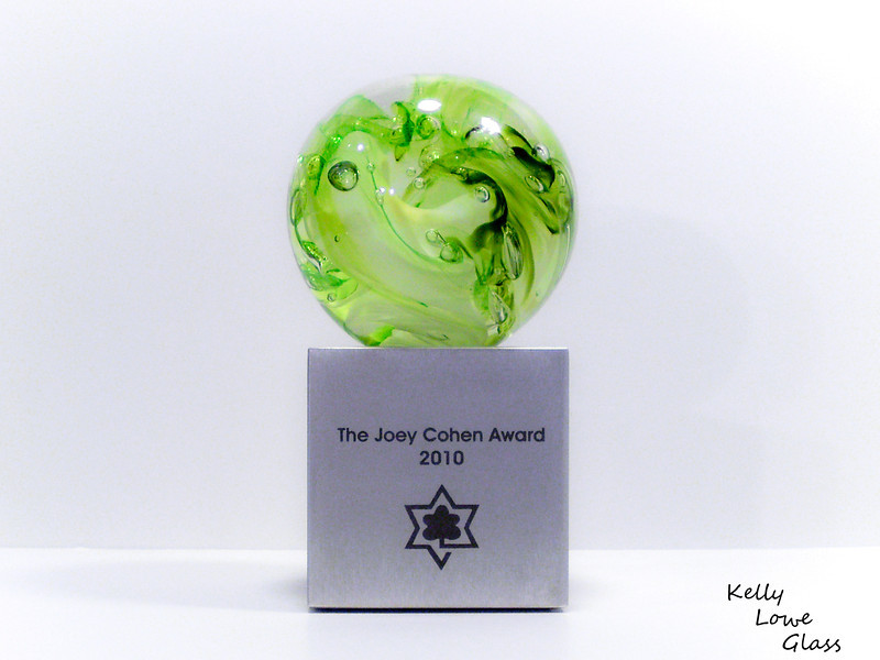 "<p></p> <h1 style=""margin:0px;""><font size=""4""><b>The Joey Cohen Award</b></font></h1> Swirling colours and air bubbles move within this glass globe, fitted atop an engraved aluminum base.  <i><a href=""/Custom/Awards-and-Commissions/"" target=""_blank"" title=""Awards and Commissions - Kelly Lowe Glass."">Click here to go to the awards and commissions information page (link opens in a new window</a></i>  <i><a href=""/Glass/Awards/"" title=""Awards Sample Gallery"">If you are not on my main gallery of sample custom awards, click here to return there now</a></i>"