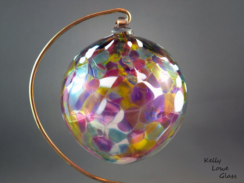 "<p></p> <h1 style=""margin:0px;""><font size=""4""><b>Traditional Hand Blown Christmas Ornaments</b></font></h1> Individually hand blown using the same methods glassblowers have used since antiquity, these ornaments are a holiday classic  just like great great great great great grandma may have had.   I make these Christmas balls in a variety of colours, (see the link below for more examples) including the multicoloured one pictured here. Each ornament begins life as liquid glass in a special glassblowing furnace, from which it's pulled and blown by mouth into a hollow sphere. During this process colour is added, which melts and is allowed to flow and combine throughout ornament, making each ball truly one of a kind: the color will never mix in the same way twice. While the piece is still hot a small glass loop is added to the top to make for easy hanging from a Christmas Tree or any other place one could wish to hang it, and finally it is slowly cooled over the course of 24 hours in a special glass kiln to ensure the glass is very strong and will last a lifetime.  Diameter - Approx 9.5cm (3.75"") Weight: Approx 78g (0.17 lbs)  *Note: As each ornament is blown by mouth and is fully handmade some variation in the size of individual ornaments is to be expected. The measurements above should thus only be taken as an average, with some balls being larger and others being smaller.  <i>This piece is available in my Stoney Creek <a href=""/Site-Stuff/Contact/"" target=""_blank"">studio gallery</a>, my <a href=""http://store.kellyloweglass.com"" target=""_blank"">online store</a> (<a href=""http://store.kellyloweglass.com/ornaments/traditional-blown-glass-ornament/"" target=""_blank"">direct item link</a>) and in many local galleries. If you're interested in larger/custom orders, please <a href=""/Site-Stuff/Contact/"" target=""_blank"">contact me</a> and I'm sure we can work something out.</i>  <i><a href=""/AvailablePieces/Ornaments/"" target=""_blank"">Click here to be taken to a gallery of all my various ornament types (link opens in a new window)</a></i>"