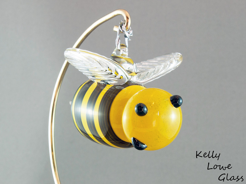 "<p></p> <h1 style=""margin:0px;""><font size=""4""><b>Hanging Glass Bee</b></font></h1> A seasonal favourite, or a feared adversary, the bee can be either depending on the individual. But where would we be without them? Less flowers, no honey and 54% less buzzing in the world... would you REALLY want that?  Some of these bees even come with crowns, showing off their royal status as queen bees.  Stinger to Nose: Approx 9cm (3.54"") Across the Wings: Approx 6cm (2.36"") Weight: Approx 150g (0.33 lbs)  *Note: As each piece is hand sculpted some variation in size is to be expected. The measurements above should be considered an average, with most pieces being slightly above or below these figures.  <i>This piece is available in my Stoney Creek <a href=""/Site-Stuff/Contact/"" target=""_blank"">studio gallery</a>, my <a href=""http://store.kellyloweglass.com"" target=""_blank"">online store</a> (<a href=""http://store.kellyloweglass.com/ornaments/glass-bee-ornament/"" target=""_blank"">direct item link</a>) and in many local galleries. If you're interested in larger/custom orders, please <a href=""/Site-Stuff/Contact/"" target=""_blank"">contact me</a> and I'm sure we can work something out.</i>  <i><a href=""/AvailablePieces/Bugs-Bugs-Bugs/"" target=""_blank"">Click here to see more of this bee and other glass insects (link opens in a new window)</a></i>  <i><a href=""/AvailablePieces/Ornaments/"" target=""_blank"">Click here to be taken to a gallery of all my various ornament types (Link opens in a new window)</a></i>"