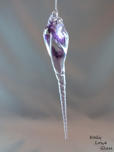 """<p></p> <h1 style=""""margin:0px;""""><font size=""""4""""><b>Glass Icicle Ornament</b></font></h1> Some winters I look up at the rooftops and sigh: """"not enough icicles!"""" I think. Then I come inside, and find no icicles. But I like icicles! How to solve this dilemma? Like most things in life this problem can be solved with glass, and hence, here I present hand sculpted glass icicles.  Length: Approx 16-25cm (6.3""""-9.85"""") Widest point: Approx 2cm (0.8"""") Weight: approx 40-85g (0.09 - 0.19 lbs)  *Note - Due to their being a variety of glass icicle sizes the figures given are a range from the smallest to the largest, with all others falling somewhere in between.  This piece is available in my Stoney Creek <a href=""""/Site-Stuff/Contact/"""" target=""""_blank"""">studio gallery</a>, my <a href=""""http://store.kellyloweglass.com"""" target=""""_blank"""">online store</a> (<a href=""""http://store.kellyloweglass.com/ornaments/glass-icicle-ornament/"""" target=""""_blank"""">direct item link</a>) and in many local galleries. If you're interested in larger/custom orders, please <a href=""""/Site-Stuff/Contact/"""" target=""""_blank"""">contact me</a> and I'm sure we can work something out.  <i><a href=""""/AvailablePieces/Ornaments/"""" target=""""_blank"""">Click here to be taken to a gallery of all my various ornament types (link opens in a new window)</a></i>"""
