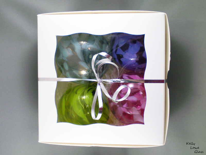 """<p></p> <h1 style=""""margin:0px;""""><font size=""""4""""><b>Box of Four Hand Blown Christmas Ornaments:</b></font></h1> Perfect as a gift for your loved ones or as an indulgence for yourself and your tree, these bundles of four Christmas Balls are the the same ornaments I sell separately, only with a fancy box and bow. Each ball is hand blown from molten glass by yours truly, and are guaranteed to add something special to this year's decorations.  These boxes can be individually made to your taste: if you'd like four pink ornaments, by all means we can do that, and that goes for any other colours I make as well. The box pictured here contains a random assortment of colours.  Each box is labelled as containing only fully handmade blown glass pieces.  Each ornament has a diameter of approximately 9.5cm (3.75""""), and they weigh an average of 78g.  <i>This piece is available in my Stoney Creek <a href=""""/Site-Stuff/Contact/"""" target=""""_blank"""">studio gallery</a>, my <a href=""""http://store.kellyloweglass.com"""" target=""""_blank"""">online store</a> (<a href=""""http://store.kellyloweglass.com/gift-boxes/blown-glass-christmas-ornaments-boxed-set-of-four/"""" target=""""_blank"""">direct item link</a>) and in many local galleries. If you're interested in larger/custom orders, please <a href=""""/Site-Stuff/Contact/"""" target=""""_blank"""">contact me</a> and I'm sure we can work something out.</i>  <i><a href=""""/AvailablePieces/Ornaments/"""" target=""""_blank"""">Click here to be taken to a gallery of all my various ornament types (Link opens in a new window)</a></i>"""