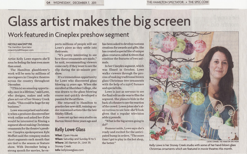 """Newspaper Article: """"Glass artist makes the big screen""""  Newspaper: The Hamilton Spectator Article Focus: Cineplex Entertainment pre-show film I appeared in Date: December 7th, 2011  The Hamilton Spectator is one of Canada's largest newspapers, with a weekly circulation of well over half a million. In my opinion they are a great supporter of the local art scene, and this article here is a perfect example of this commitment: when Cineplex Entertainment filmed a pre-film segment starring yours truly demonstrating how I make traditional blown glass Christmas ornaments, the Hamilton Spectator was there to graciously cover the event and spread the word to their readers.  I'm a tad bit on the shy side and get nervous whenever I have to stand in a spotlight, but working with professionals such as Nicole Macintyre (the writer) and Cathie Coward (the photographer) made this whole experience incredibly easy, and fun. Thank you to them both, and to the Spectator for their ongoing support of local artists!  To view the newspaper's online version of this article please click the following link: Glass Artist Makes the Big Screen (opens in a new window)."""