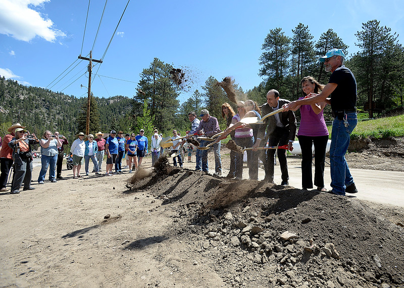 Steve and Becky Childs, far right, owners of the Glen Haven General Store, and architect and part-time resident Michael Tavel, center right, help toss shovels of dirt Thursday, June 1, 2017, during a groundbreaking ceremony for the new Glen Haven Town Hall and Community Building. The new town hall will replace the former building that was washed away by the 2013 flood. (Photo by Jenny Sparks/Loveland Reporter-Herald)