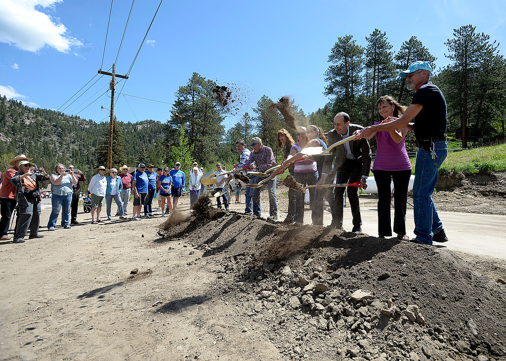 . Steve and Becky Childs, far right, owners of the Glen Haven General Store, and architect and part-time resident Michael Tavel, center right, help toss shovels of dirt Thursday, June 1, 2017, during a groundbreaking ceremony for the new Glen Haven Town Hall and Community Building. The new town hall will replace the former building that was washed away by the 2013 flood. (Photo by Jenny Sparks/Loveland Reporter-Herald)