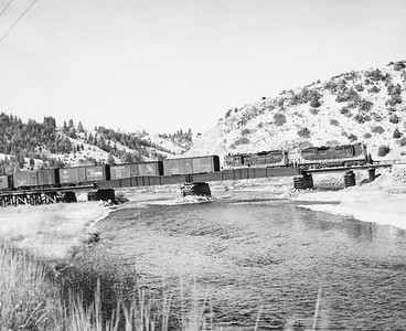 2009.002.017--glenn guerra collection 8x10 print--NP--company PR photo of EMD diesel locomotive 270 on freight train crossing bridge en route to mining operation--near Phosphate MT--no date