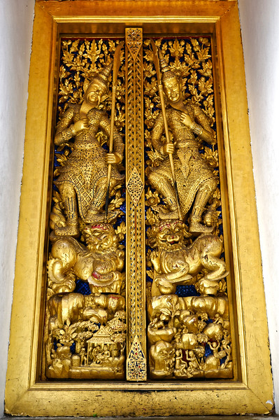 Carved guardian figures on a temple door. The narrower dimension seen at the top is only slightly the result of camera-lens distortion. This is actually a traditional Thai door style: narrower at the top than at the base.