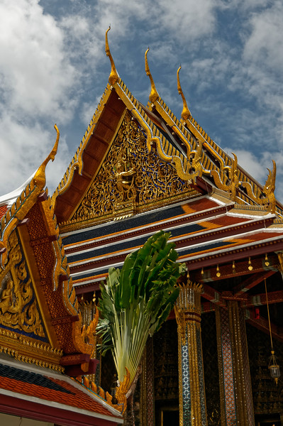 The resplendent <i>ubosot</i> or ordination hall in which the Emerald Buddha is housed is seen in the background. The Hindu god Vishnu astride Garuda appears on the building's gableboard.