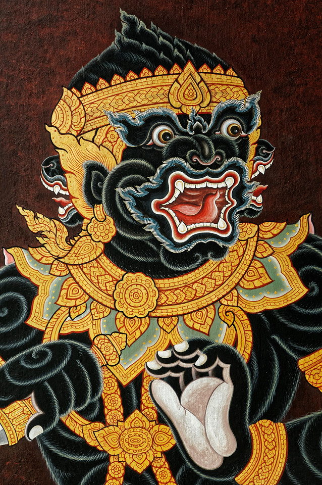 In this detail of a fierce-looking multi-faced creature, more <i>kanok</i> are seen emanating from the collar and surrounding the ear. Even the stylized white and gray eyebrows encircling the eyes and the similarly shaped fur surrounding the mouth—perhaps the tongue itself—seem to be <i>kanok</i>-inspired.
