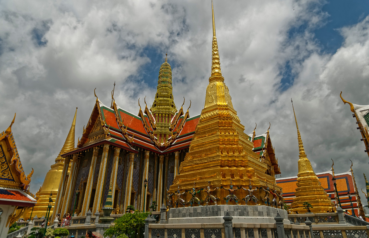 This view of the central area of the temple takes in the Royal Pantheon, Prasat Phra Thep Bidon, center background, with a partial view of the Golden Chedi, the temple's main <i>chedi</i> or stupa, left background, and two smaller <i>chedi</i> on the right built by Rama I in honor of his father and mother.