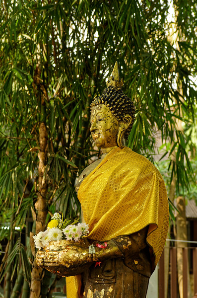 Standing Buddha image with flower offerings