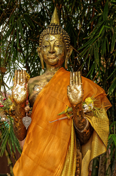 Another standing Buddha figure, here with both hands raised in <i>abhaya</i> mudra, a gesture of calming or reassurance. Gold-leaf offerings have been generously applied to the image by worshippers as a merit-making gesture.