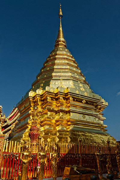 Clad entirely in gilded copper sheeting, Wat Doi Suthep's glorious <i>chedi</i> is among the most magnificent in Thailand. The deep redention of its high base is echoed above by the plinths, relic chamber, and upper structure, all octagonal in plan. The <i>chedi</i> is said to contain a sacred relic that the monk Sumana brought from Sukhothai in 1371.