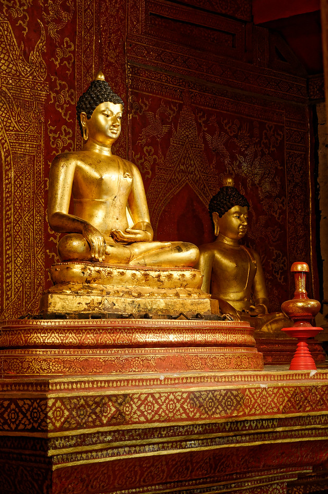 Phra Singh's smaller assembly hall also houses the Phra Sihing Buddha, seen here on the left. The gilded-bronze image's head was stolen in 1922, later replaced by a replica placed over the original body.
