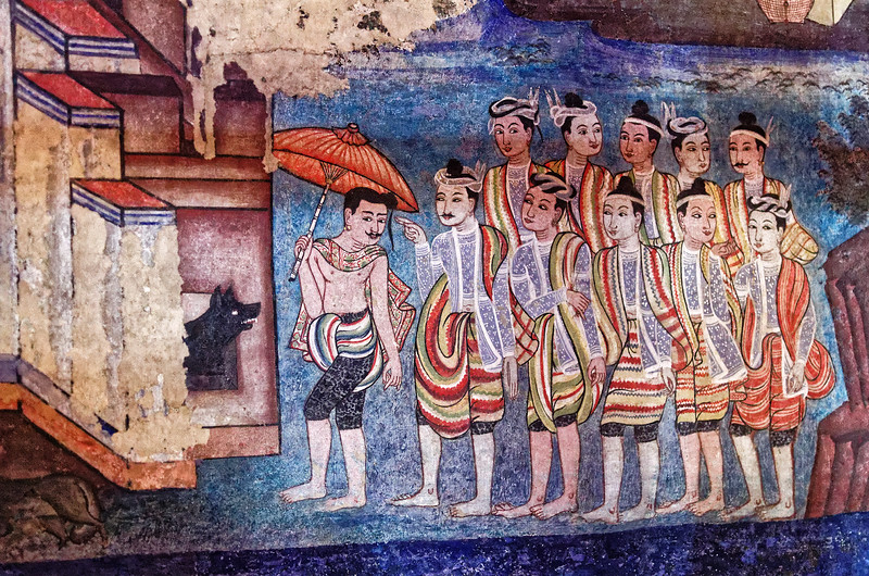 In another detail from the murals, Shan men are seen here in their turbans and striped shawls. Their legs are heavily tattooed, more apparent on the Tai Lu man holding the red umbrella, whom the Shan are following.