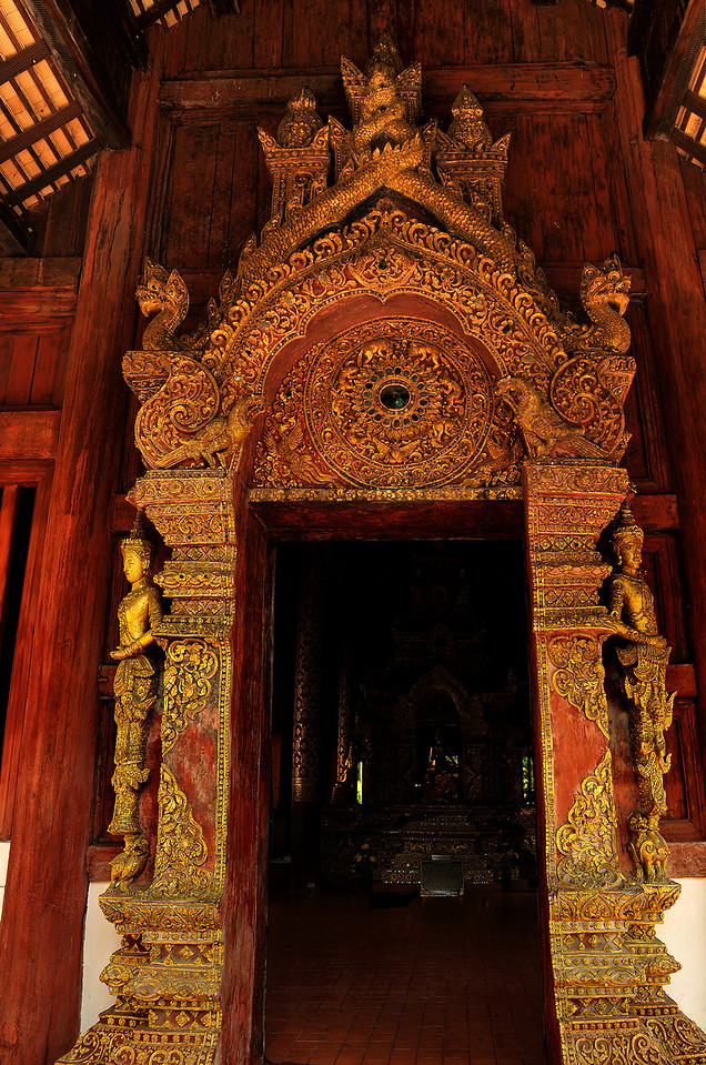 The south portico entrance to Wat Phra Singh's ordination hall is adorned with gilded decorations covering the columns and the elaborately carved archway. The latter features a small menagerie of fantastic creatures likely meant to serve as guardians. Flanking the entry are two <i>thewada</i> similar in appearance to those modeled in stucco around the base of the temple's library.