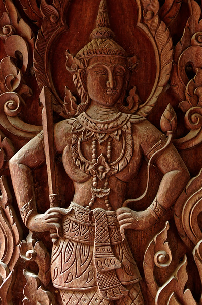 Detail of a guardian figure on the carved wooden door of a small chapel housing a reclining Buddha to the rear of Wat Phra Singh