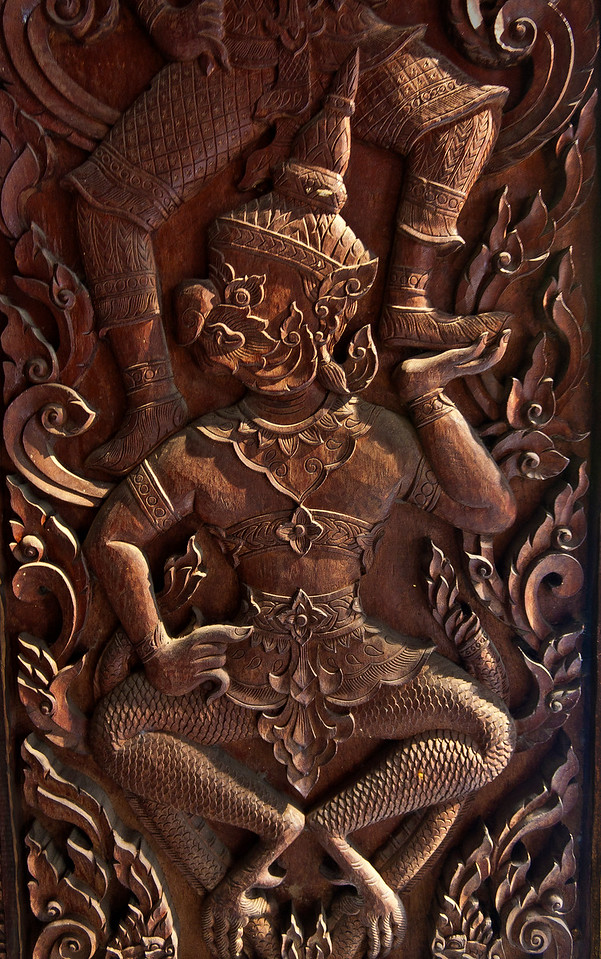 Another carved door detail depicts a part-bird part-human figure called a <i>garuda.</i>