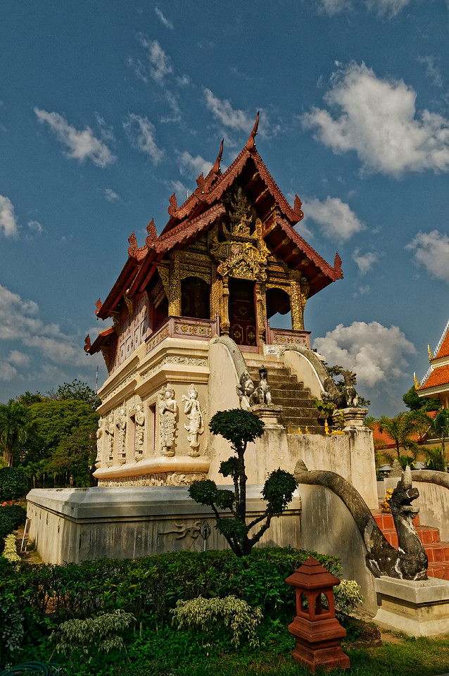 The <i>ho trai</i> or library at Wat Phra Singh, built in 1477, is a jewel of Lanna-style architecture. Beneath the triple-tiered roof, its elaborate gable is decorated with designs in stucco, glass mosaic, and gilded lacquer, all sitting atop a stucco-covered base enlivened with playful carvings of guardian <i>thewada</i> figures and a variety of fantastic animals. <i>Ho trai,</i> originally used to store palm leaf manuscripts, were generally built on stilts or otherwise raised above ground to protect the manuscripts from termites and from excessive humidity.
