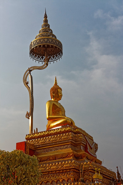 The multi-tiered umbrella, called a <i>chat,</i> above the Buddha image, symbolizes spiritual power.