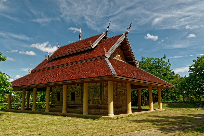 The ordination hall or <i>sim</i> at Wat Sra Bua Kaeo has a double-tiered gabled roof above a hipped lower tier, a design commonly found in Isaan temples. Unlike at Wat Srathong, however, the hipped roof extends well beyond the main structure below and is supported by columns all around, thus creating a covered walkway that surrounds the main structure and that also affords greater protection from the elements to the exterior paintings.