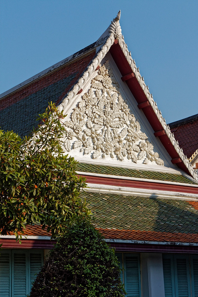 An elaborately carved floral design on the gableboard of a minor building on the temple grounds