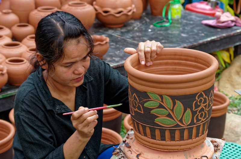 Among those demonstrating some of the local crafts, a potter was busily making vases, while this woman painted them with decorative designs.