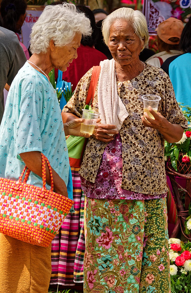 An apparently serious conversation between these two women as they savored some of the free herbal drinks on hand. The women of Isaan seem to delight in wearing multi-patterned outfits.