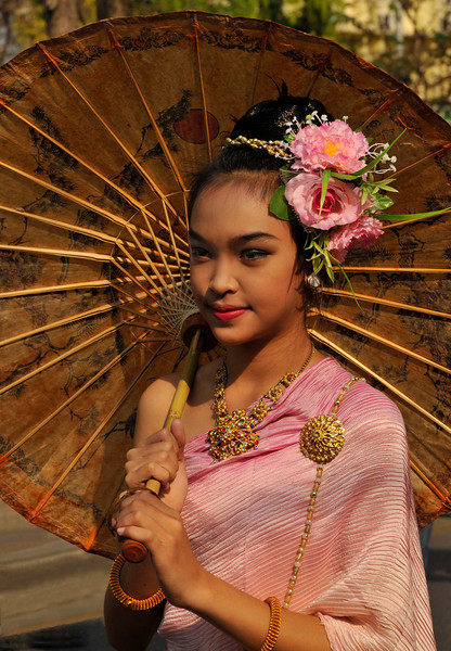 This young Lanna woman is dressed in elegant Thai silk and is holding a traditional mulberry-paper and bamboo umbrella.