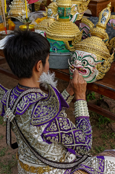 An actor tweaks a mask prior to the performance.