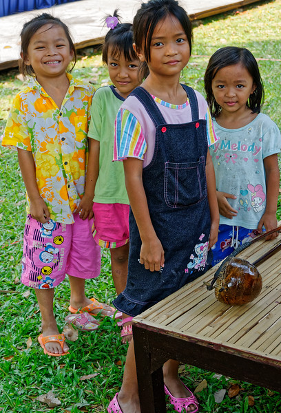 Happily taking in the music at the festival, these little Isaan girls didn't know whether to smile or to be bashful in front of the camera .
