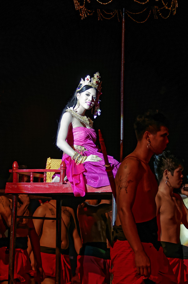 The festival queen arrives, transported on a litter with male bearers.