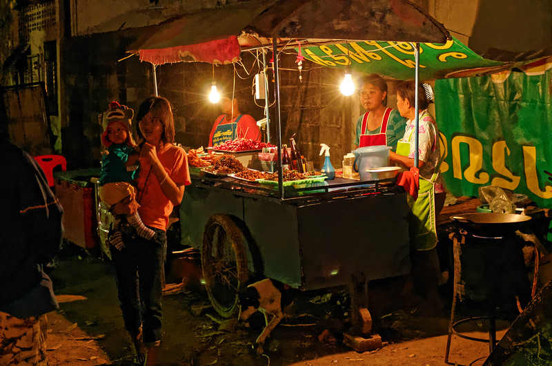 In a dimly lit corner at a local carnival in Isaan, these women were selling fried grasshoppers and crickets as well as chicken and sausages.
