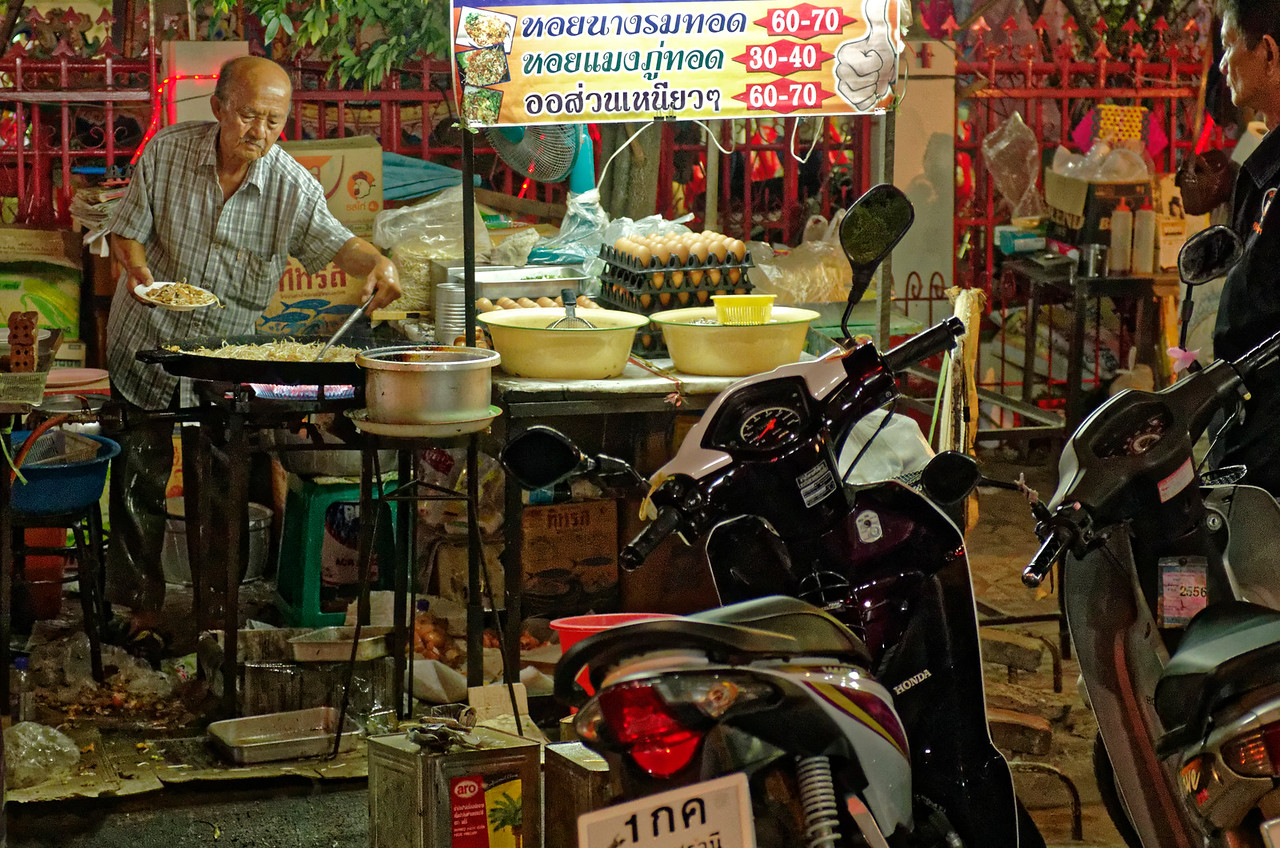 This gent was preparing fried oysters and mussels with bean sprouts for the customer partially seen at far right.