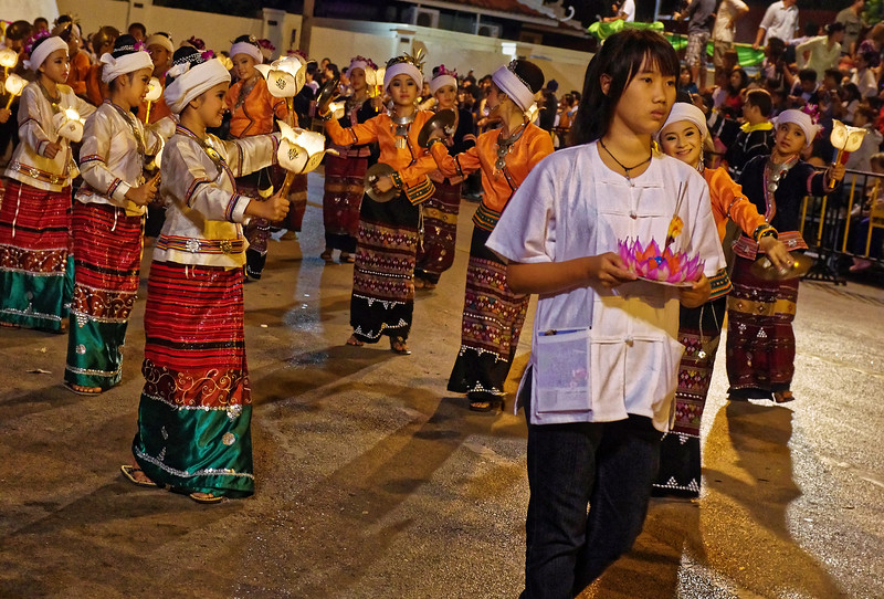 The girl in the foreground carries a <i>krathong,</i> as will many others in the parade. The <i>krathong</i>   will later be floated on the Ping River, which runs through the city.