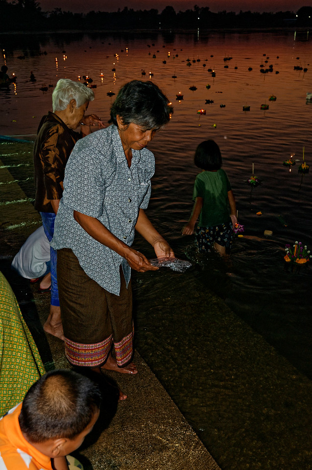 Some festival-goers release small fish into the water as a means of making merit.