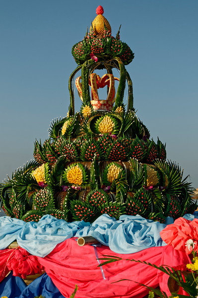 Greenery for the <i>krathong</i> is fashioned from banana leaves. The yellow pods seen here in this <i>krathong</i> from Sisaket are silkworm cocoons. The red accents were created from cut and folded flower petals.