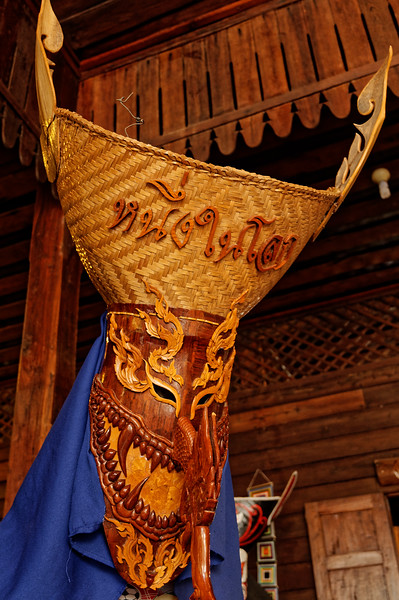 "To complete the mask, cloth is sewn onto the back in order to hide the back of the wearer's head and neck. Some masks also have ""horns"" attached, which are cut from coconut-palm lobes."