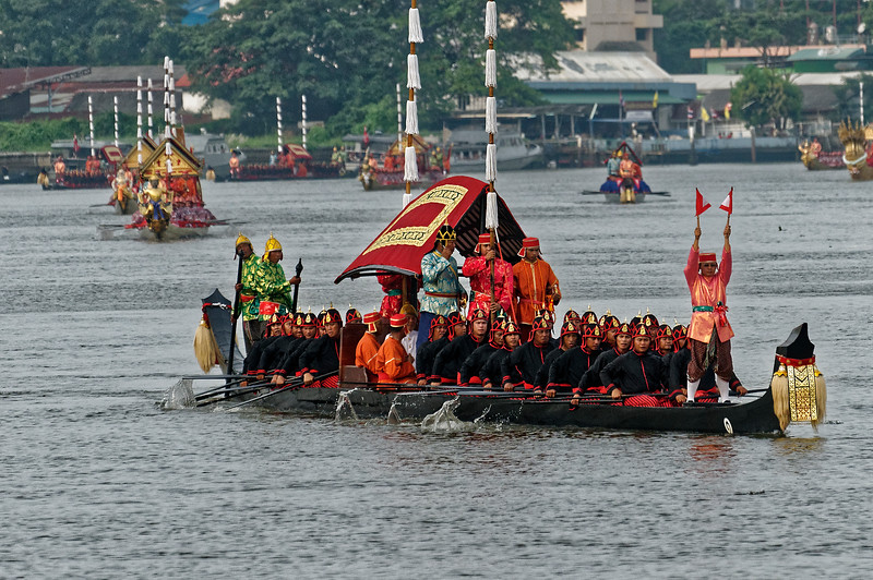 Crew members of the escort boats wear an assortment of colorful uniforms based on their posts. The boat's officer wears a floral-patterned light-blue jacket over dark-blue trousers. Standing next to him in the photo above is a red-clad standard bearer and a bugler dressed in orange. The signalman is at the front of the boat. The steersmen wear gold-patterned green jackets and golden headgear.
