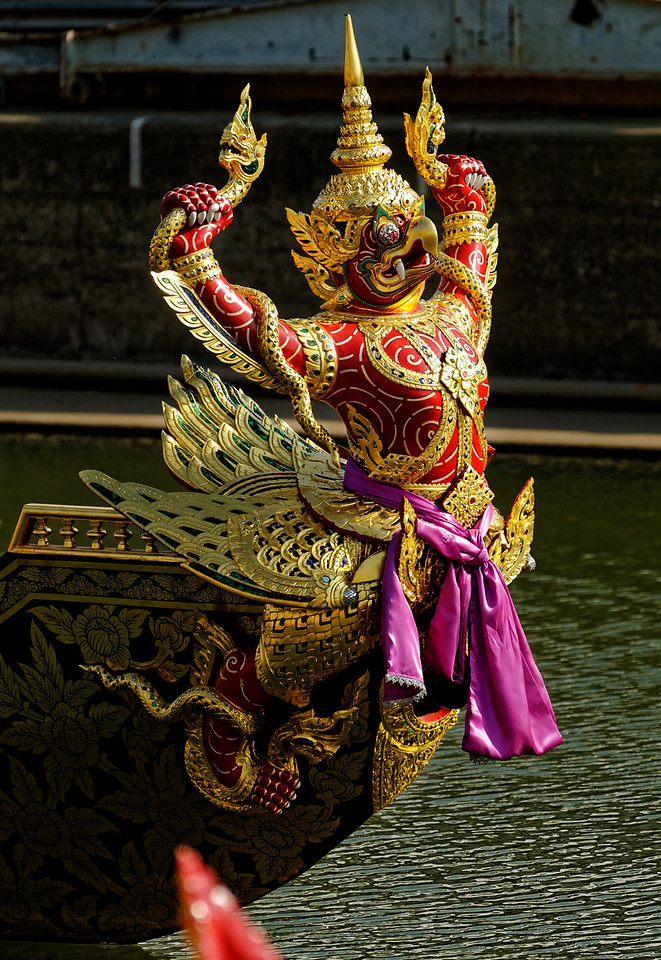 "The elaborately carved and gilded figureheads and hulls of the royal barges incorporate iconography with origins in ancient Brahmanism and Hinduism. The figure seen here is the Garuda, part-human part-bird creature who is arch enemy of the serpentlike <i>naga</i> that he holds in his hands. This particular creature's name is Krut Hern Het, ""Flying Garuda."""