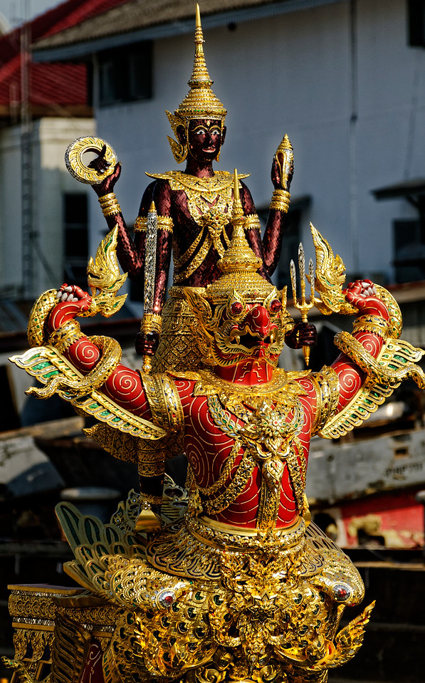 Garuda, seen in yet another guise, is also the traditional mount of Vishnu, one of three principal Hindu deities, who stands astride Garuda here. One incarnation of Vishnu is Rama, the hero of the <i>Ramayana/Ramakien.</i> Thailand's kings of the current Chakri dynasty, which dates from the late 18th century, are considered incarnations of Rama, while the Garuda is Thailand's national symbol.