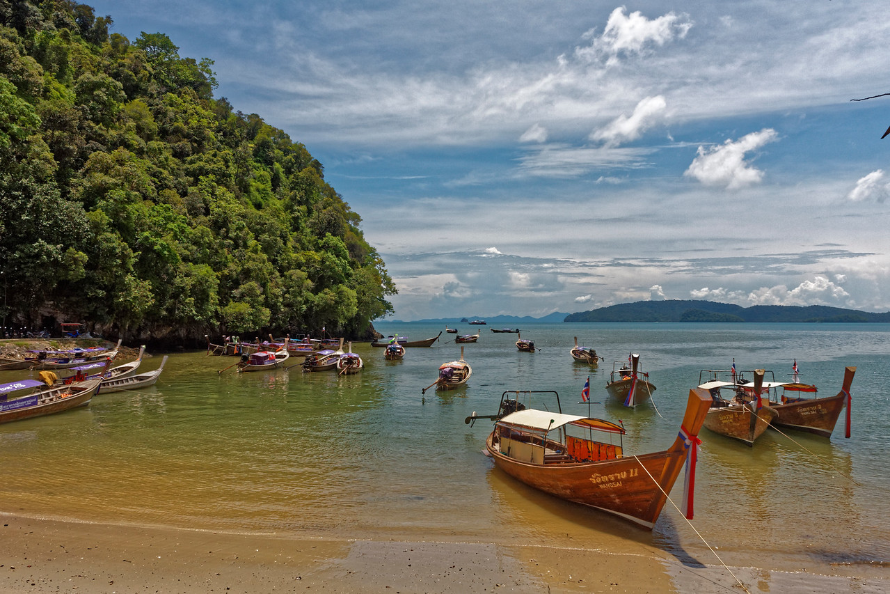 Longtail boats in a cove, and offshore islands, seen from the beach at Ao Nang, on the Andaman Sea in the southern province of Krabi