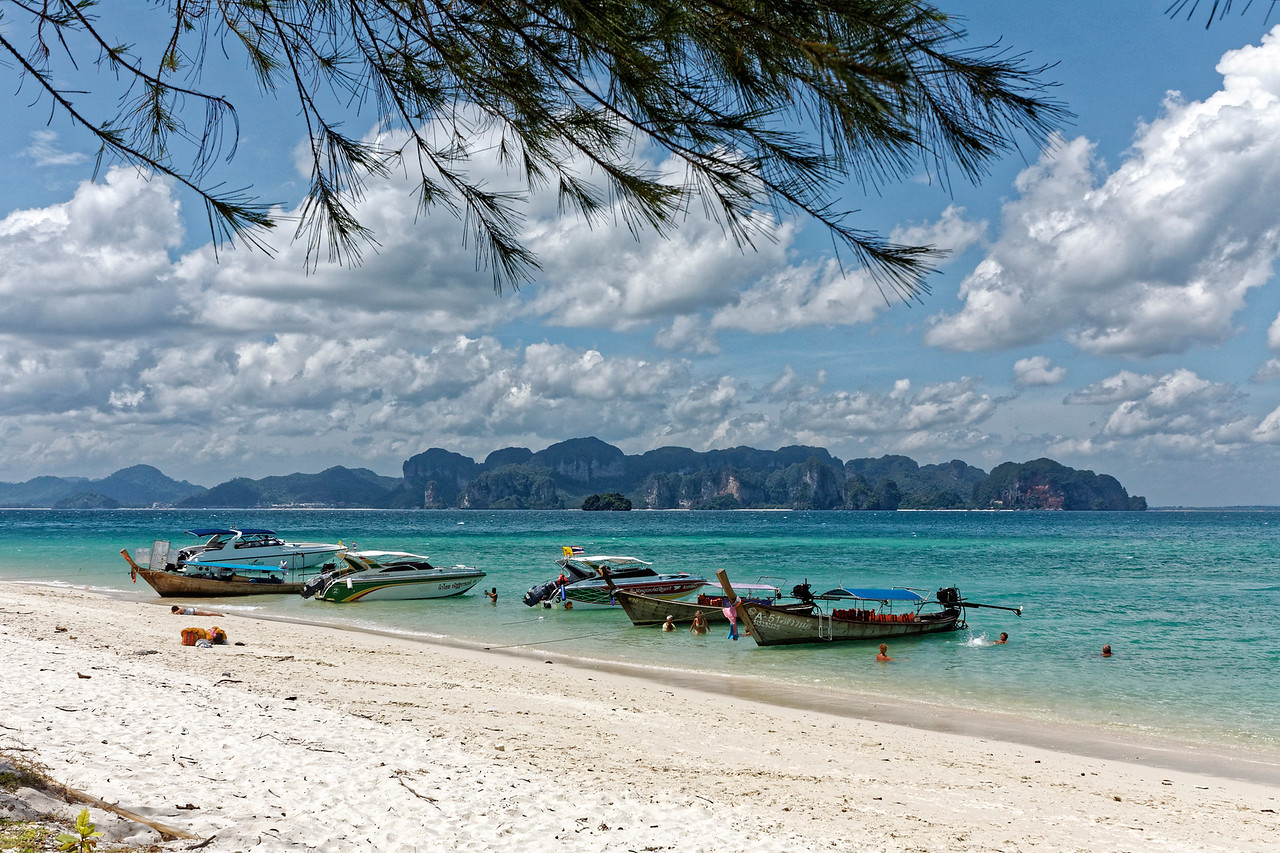 Speedboats and longtail boats at one of the beaches that encircle Poda