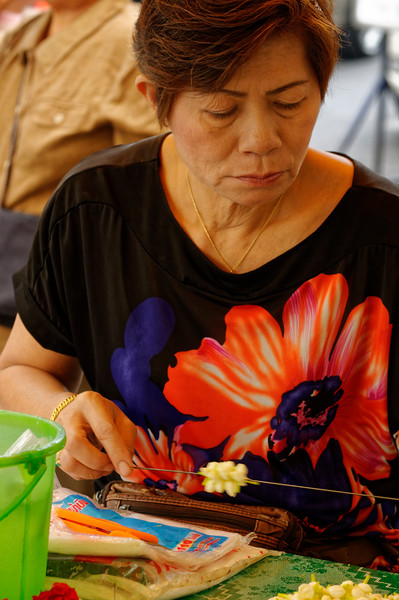 Stringing flowers for a garland to sell at a Bangkok street stall