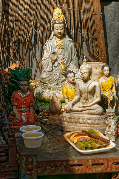 Open shrine in an alleyway in Thonburi, with offerings
