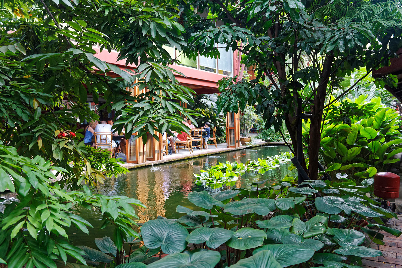 View of the pond and restaurant at the Jim Thompson House, offering a serene respite from the frenzy of the city's streets