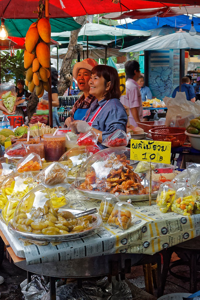 Fresh mangoes and pickled fruit offered by these sidewalk vendors
