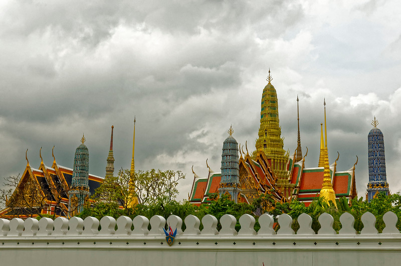 Behind the wall, the tops of structures at Wat Phra Kaeo, Temple of the Emerald Buddha, on the grounds of the Grand Palace