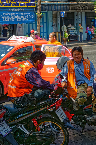 Motorcycle taxi drivers provide another means of transportation in the city, their fares riding pillion.