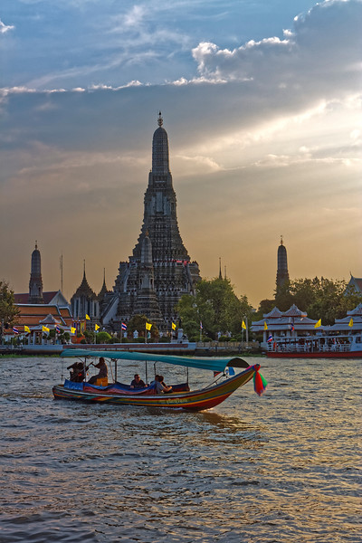 Boats both large and small that ferry passengers along the Chao Phraya River are another means of beating Bangkok's traffic-jammed streets. Seen in the background is Wat Arun, Temple of the Dawn.